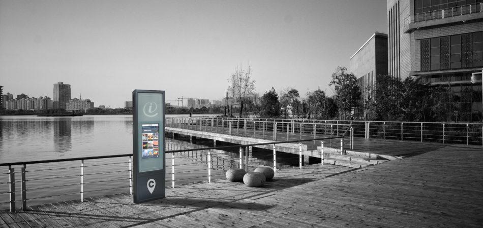 un totem interactif en extérieur à côté d'un plan d'eau